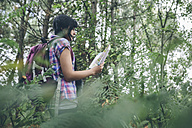 Young woman with backpack looking at hiking map in the forest - DAPF000271