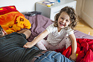Father and happy daughter on bed - DIGF000989