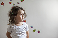 Girl standing in front of wall decorated with flowers - DIGF000995