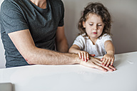 Daughter attaching plaster to father's hand - DIGF000998
