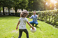 Father and daughter playing with ball in park - DIGF001022