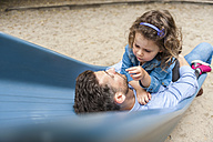 Father with daughter on playground slide - DIGF001028