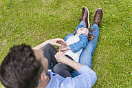 Father tickling daughter on meadow in park - DIGF001043