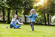 Father and daughter playing on meadow in park - DIGF001046