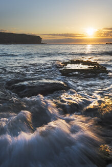 Australia, New South Wales, seascape with rushing water and rising sun and backlit, waves - GOAF000012