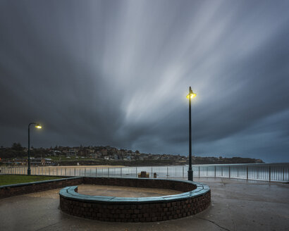 Australia, New South Wales, Tamarama, bench and beach, dramatic clouds in the evening - GOAF000075