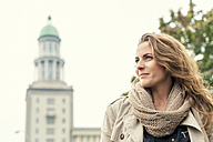 Germany, Berlin, smiling blond woman looking at distance - TAMF000553