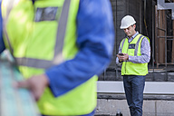 Men with cell phone on construction site - ZEF009428