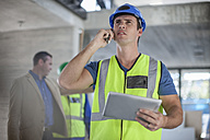 Man with cell phone and tablet on construction site - ZEF009440