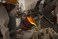 Worker casting metal in a foundry - ZEF009468