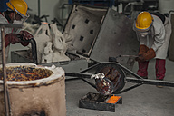 Workers casting metal in a foundry - ZEF009483