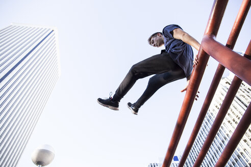 Spain, Madrid, man jumping over a fence in the city during a parkour session - ABZF000988