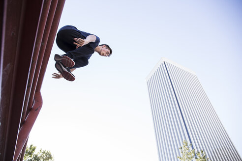 Spain, Madrid, man jumping over a fence in the city during a parkour session - ABZF000991