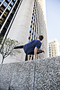 Spain, Madrid, man jumping over a wall in the city during a parkour session - ABZF000994