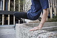 Spain, Madrid, man jumping over a wall in the city during a parkour session - ABZF000997