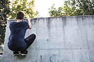 Spain, Madrid, man climbing on a wall, during a parkour session - ABZF001006