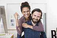 Man carrying happy woman piggyback in office - RBF004912