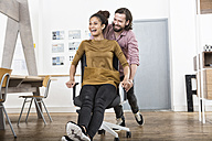Man pushing happy woman on office chair - RBF004921