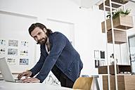 Man using laptop in office - RBF004930
