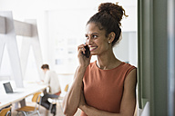 Smiling woman in office on cell phone - RBF004948