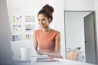 Smiling woman sitting at office desk using laptop - RBF004957