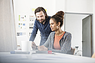 Two colleagues working together at office desk - RBF004960