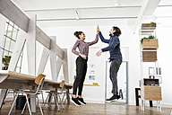 Two happy colleagues in office jumping and high fiving - RBF004975