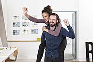 Man carrying happy woman piggyback in office - RBF004978