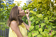 Woman smelling apple in the garden - KNTF000460