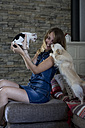Smiling woman with her dogs at home - MAUF000814