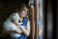 Smiling woman with cat on her arms looking through window - MAUF000820
