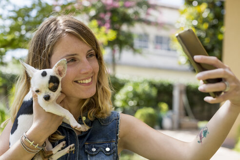 Woman taking selfie with her Chihuahua in the garden - MAUF000823