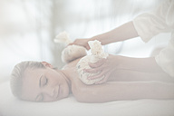 Masseuse placing aromatherapy sachets on woman's back - ZEF009569