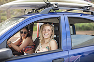 Two happy young women in car with surfboards on roof - ZEF009617