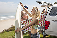 Friends taking out surfboard and beach chair from car at the coast - ZEF009620