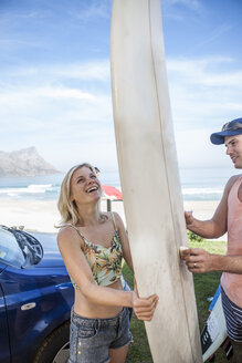 Happy couple with surfboard at the coast - ZEF009623