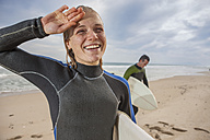 Smiling young woman with surfboard on the beach - ZEF009632