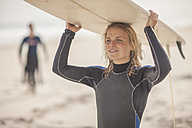 Young woman carrying surfboard on her head on the beach - ZEF009635