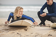 Man instructing woman on surfboard on the beach - ZEF009638