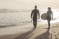 Couple with surfboards walking on the beach at sunset - ZEF009644