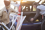 Happy couple packing their items in the car at sunset - ZEF009647
