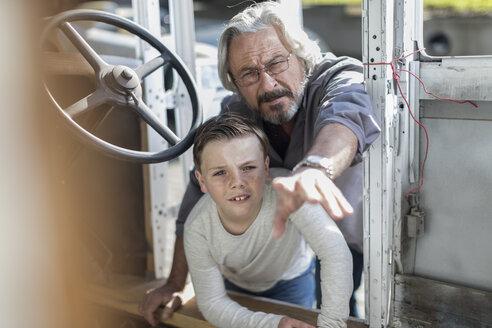 Senior man explaining old car to boy - ZEF009650