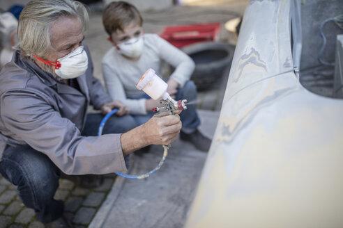 Senior man spraying on car with boy watching him - ZEF009683