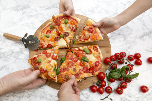 Vegetarian pizza with mozzarella and tomatoes, hands taking peace of pizza - SARF002855