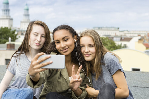 Germany, Berlin, three teenage girls sitting on roof top taking selfie with smartphone - OJF000146