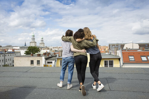 Germany, Berlin, back view of three teenage girls standing arm in arm on roof top - OJF000149