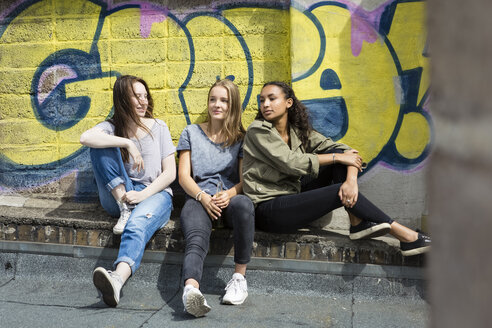 Three teenage girls relaxing on roof top in front of graffiti - OJF000152