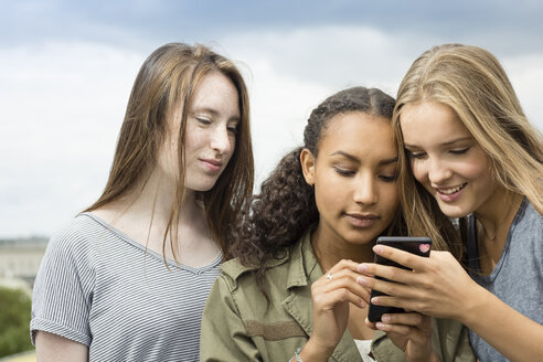Three teenage girls on roof top looking at cell phone - OJF000158