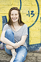 Portrait of laughing teenage girl with braces sitting in front of graffiti - OJF000161