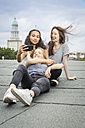Germany, Berlin, three friends sitting  on roof top taking selfie with smartphone - OJF000164